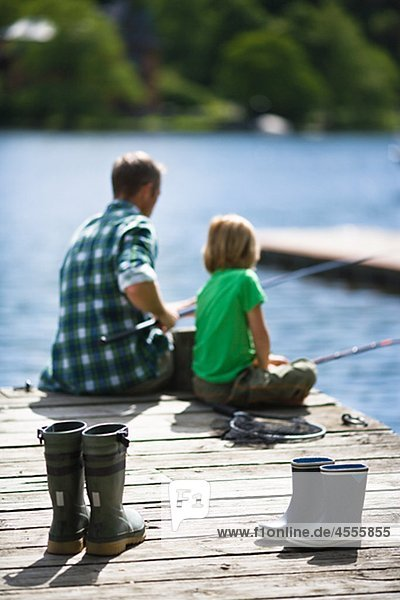 Father with son fishing  rubber boots on foreground