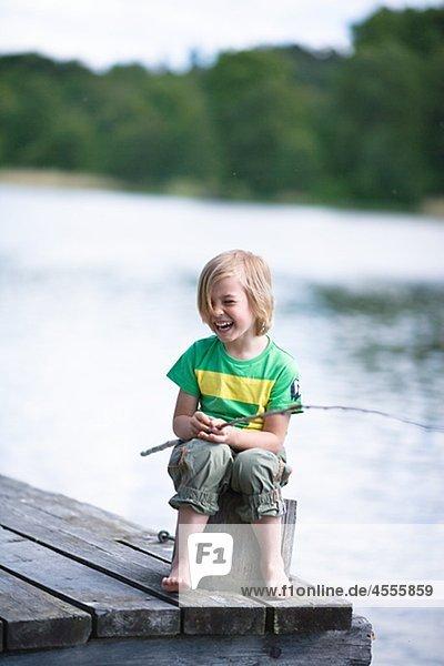 sitzend lachen Junge - Person Steg angeln Stange