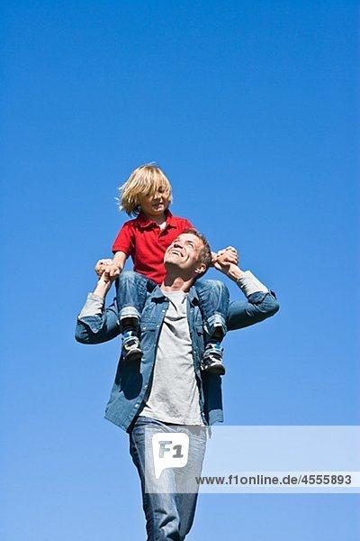 Vater Piggy Backing Tochter gegen Wolkenloser Himmel