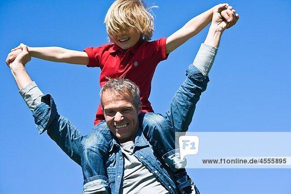 Piggyback Portrait von Vater und Sohn gegen Wolkenloser Himmel  in hellem Sonnenlicht