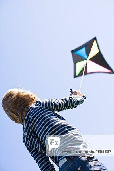 Boy flying Kite in hellem Sonnenlicht  gegen Wolkenloser Himmel