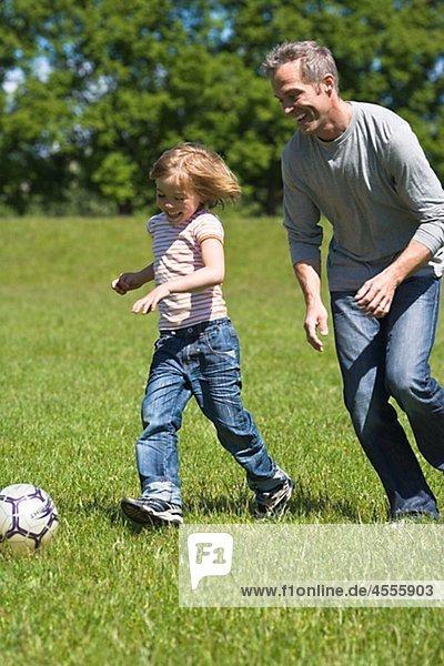 Vater und Sohn spielen Fußball in hellem Sonnenlicht