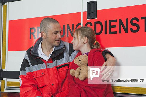 Krankenwagenmann  der sich um das Mädchen im Bus kümmert.