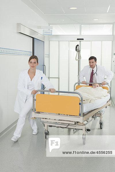 Krankenschwester und Arzt schieben Bett in der Halle