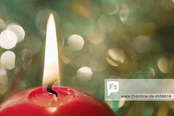 Weihnachtskerze vor Weihnachtsdekoration  Nahaufnahme