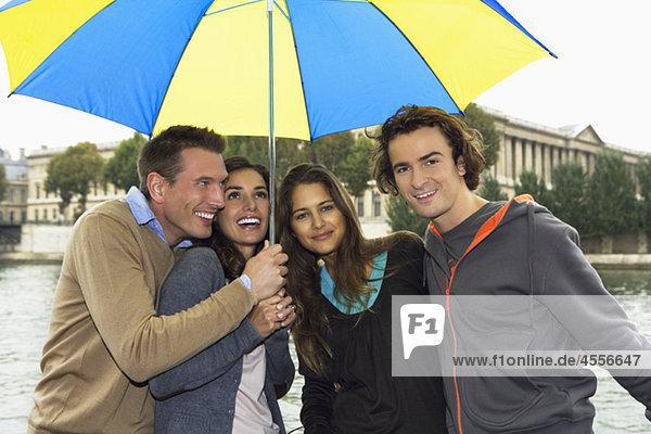 Zwei Paare unter Regenschirm  Seine  Paris  Frankreich