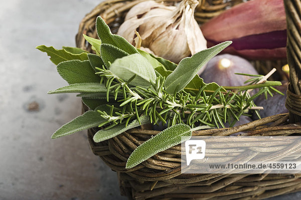 Frische Kräuter in Korb mit Knoblauch  Schalotten und Feigen