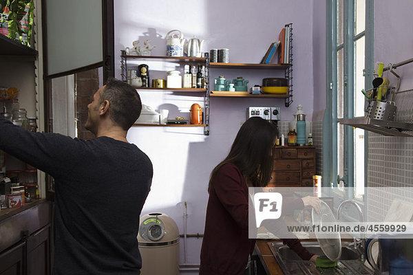 Paar in der Küche zusammen  Frau beim Abwaschen  Mann beim Öffnen der Speisekammer