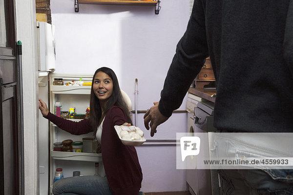 Frau  die dem Mann Zutaten aus dem Kühlschrank übergibt