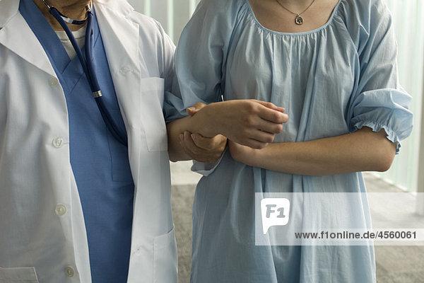 Patient hält sich zur Unterstützung am Arm der Krankenschwester fest.