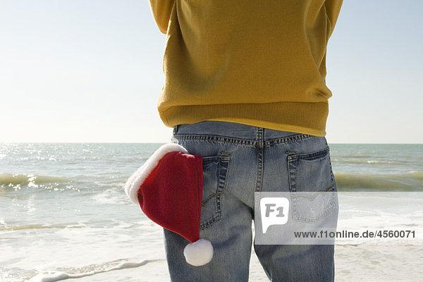 Mann am Strand stehend mit Blick auf den Strand,  Nikolausmütze in der Gesäßtasche