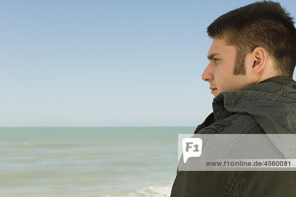 Junger Mann am Strand betrachtet nachdenklich die Aussicht