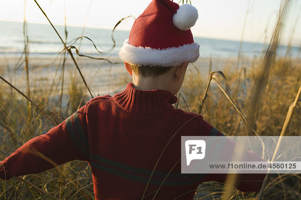 Junge mit Nikolausmütze auf Entdeckungsreise im Freien