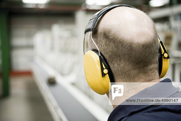Carpet factory worker wearing sound-proof protective headphones