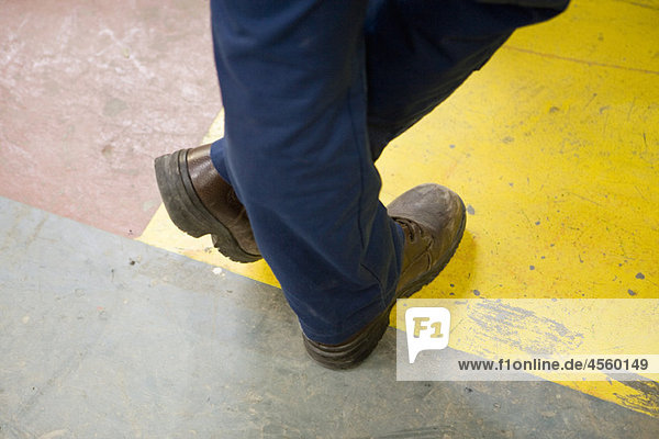 Factory worker wearing protective boots  standing with legs crossed at ankle  cropped