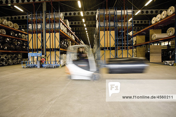 Forklift transporting roll in carpet tile factory warehouse