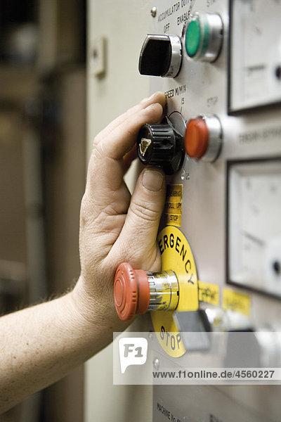 Einstellknopf für die Arbeitsgeschwindigkeit am Bedienfeld der Schermaschine in der Teppichfliesenfabrik
