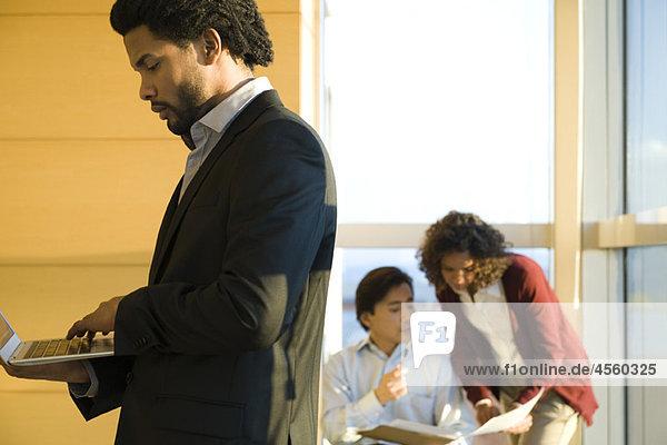 Führungskraft im Flur  mit Laptop  Kollegen im Hintergrund