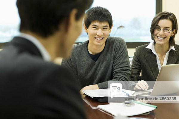 Führungskräfte im Meeting  die sich gegenseitig anlächeln
