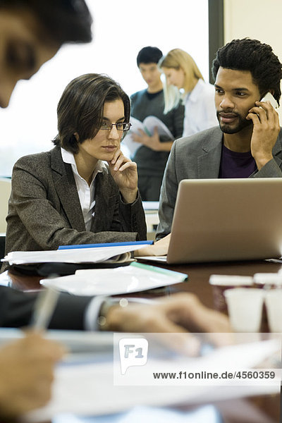 Executives working together  one using cell phone