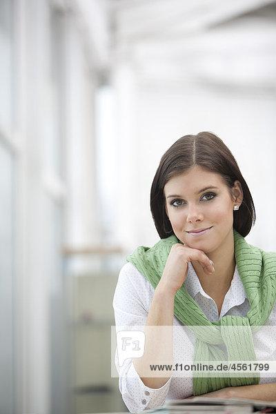 Portrait einer jungen Frau an Schreibtisch sitzen