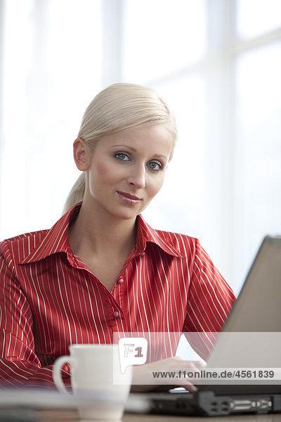 Porträt der jungen geschäftsfrau arbeiten mit Laptop-computer