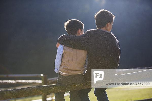 Rückansicht zweier jungen Zaun sitzend