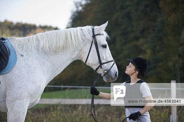 junge hält White horse