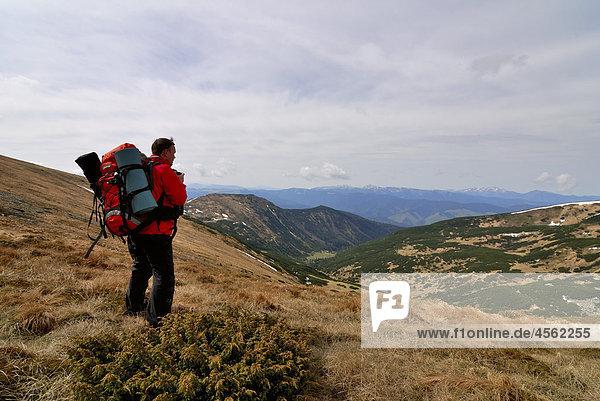 hiker on Chornogora Ridge of Carpathian Mountains looking at Lake Brebeneskul