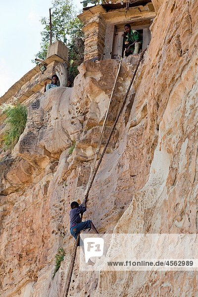 Debre Damo  climbing the vertical cliff  which is the only access to the monastery of Debre Damo The monastery Debre Damo is one of the important religious places of the ethiopian christian orthodox church and was founded in the 6th century located high