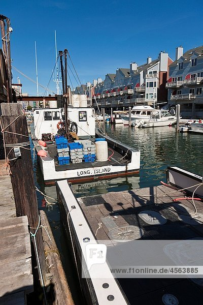 Private and commercial fishing boats docked at wharf near apartments and condominiums in Portland  Maine