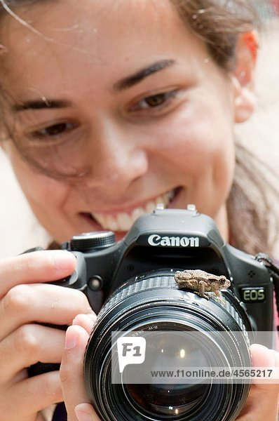 Young photographer woman using Canon brand camera funnily looking at a common Toad Bufo bufo juvenile on the lens and smiling