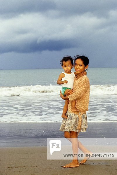 little girl and baby on the beach  Sumatra island  Republic of Indonesia  Southeast Asia and Oceania