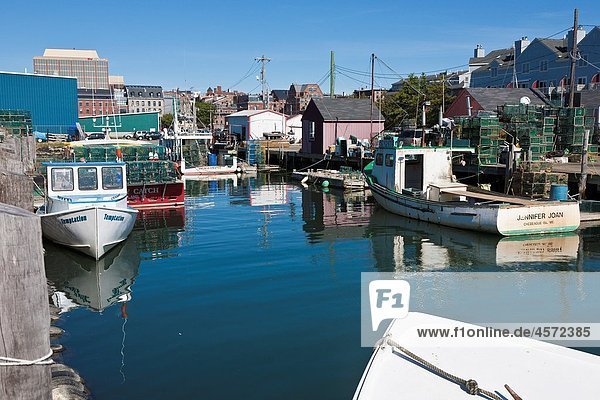 Commercial lobster fishing boats tied to pier in Portland  Maine