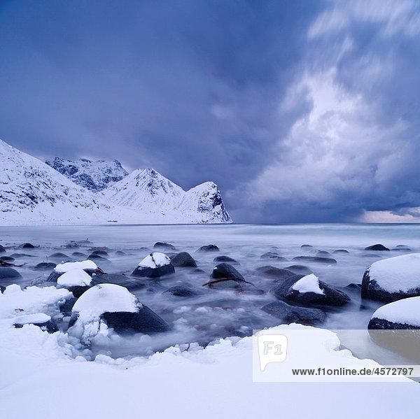 Winter storm over snow covered beach  Unstad  Lofoten islands  Norway