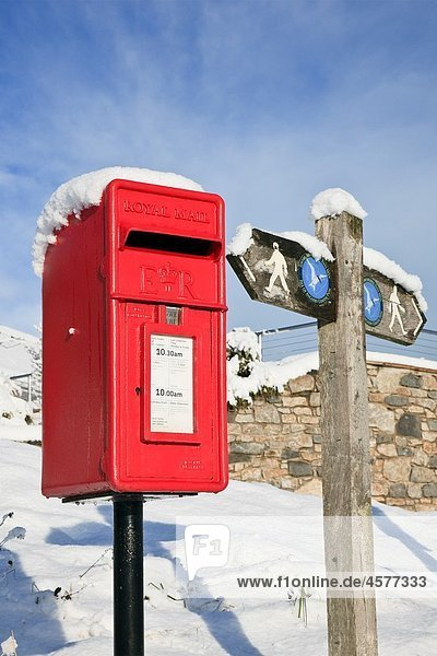 Red Wharf Bay  Isle of Anglesey  North Wales  UK  Europe Red postbox and coastal path signpost in the snow