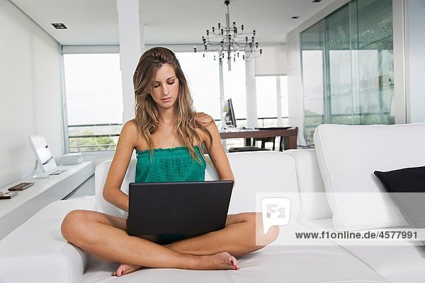 Blonde woman with laptop in the living room