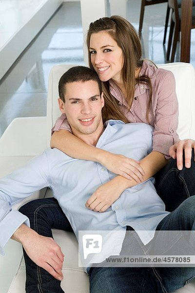 Portrait of a couple in sofa smiling at camera