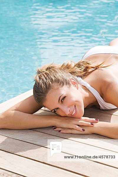 Portrait of a beautiful blonde woman relaxing by the pool