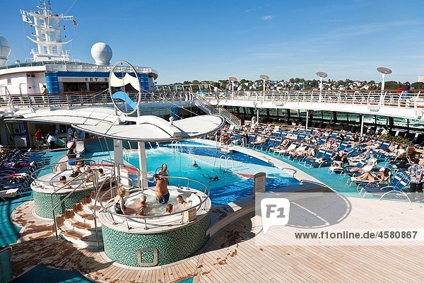 Senior men and women sit in hot tub and on lounge chairs on the deck of Royal Caribbean´s Jewel of the Seas cruise ship