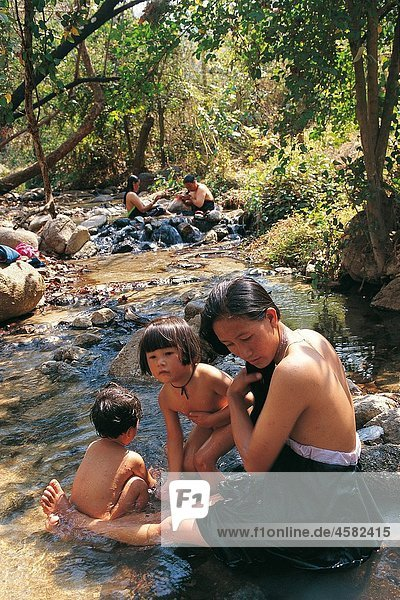 WOMAN AND CHILDREN BATHING IN THE HOT SPRINGS  PAI REGION  THAILAND
