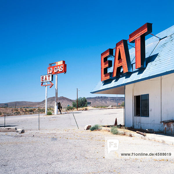 ¥Eat¥ and ¥gas¥ signs outside an abandoned gas station and diner off Interstate 15. California  USA