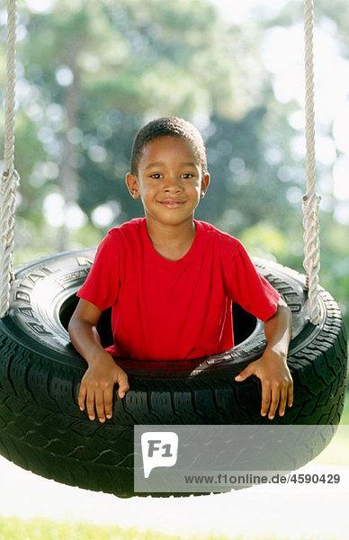 boy in a tire swing
