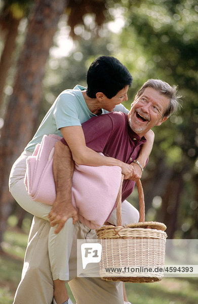 man gives a woman a piggy back ride to a picnic