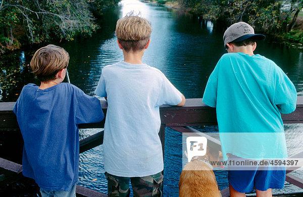 boys fishing from a bridge