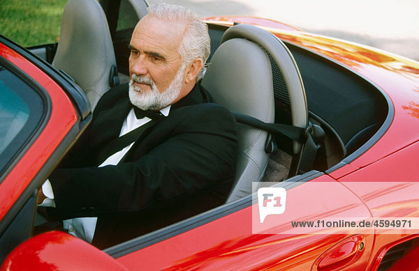 man driving a red convertible