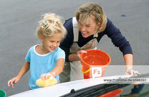mother and daughter washing a car