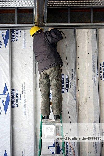 Carpenter on ladder installing steel studs