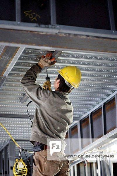 Carpenter installing steel ceiling studs