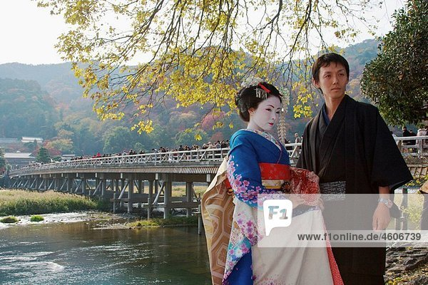 A Japanese man wearing a traditional kimono and a woman dressed up as a geisha are standing infront of the famous bridge Togetsu-kyo  the dominant landmark in Arashiyama with autumn leaf colors in the back ground